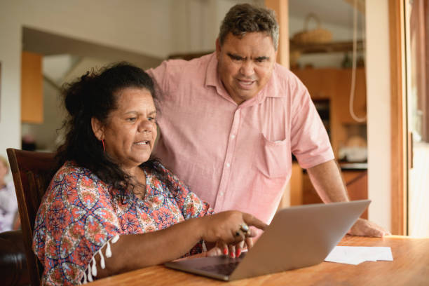 Mature couple using laptop with woman pointing stock photo