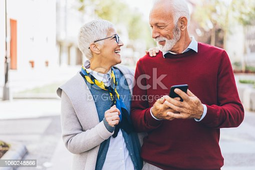 Happy smiling Mature couple using smartphone outdoor on the street