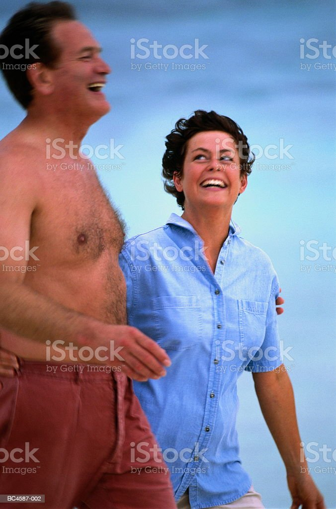 Mature couple walking along beach royalty-free stock photo