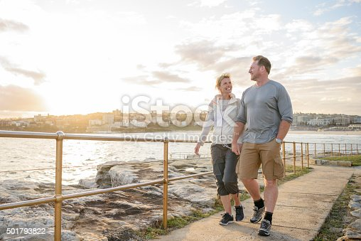 Couple walking by sea on path on vacation in Sydney, Australia.