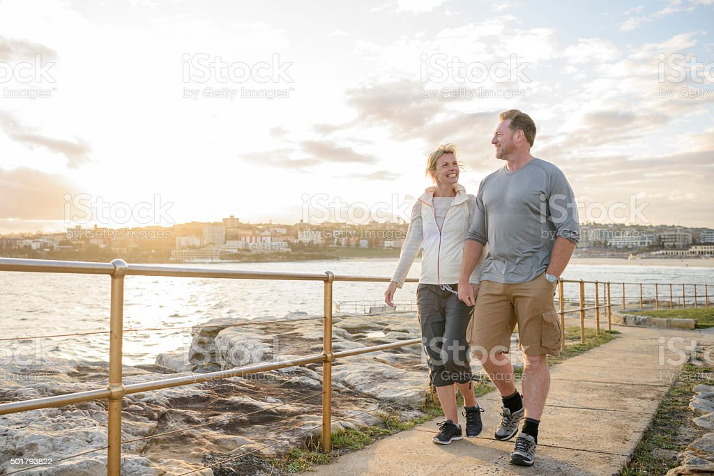 Mature couple walking on boardwalk at sunset, Bondi Beach stock photo