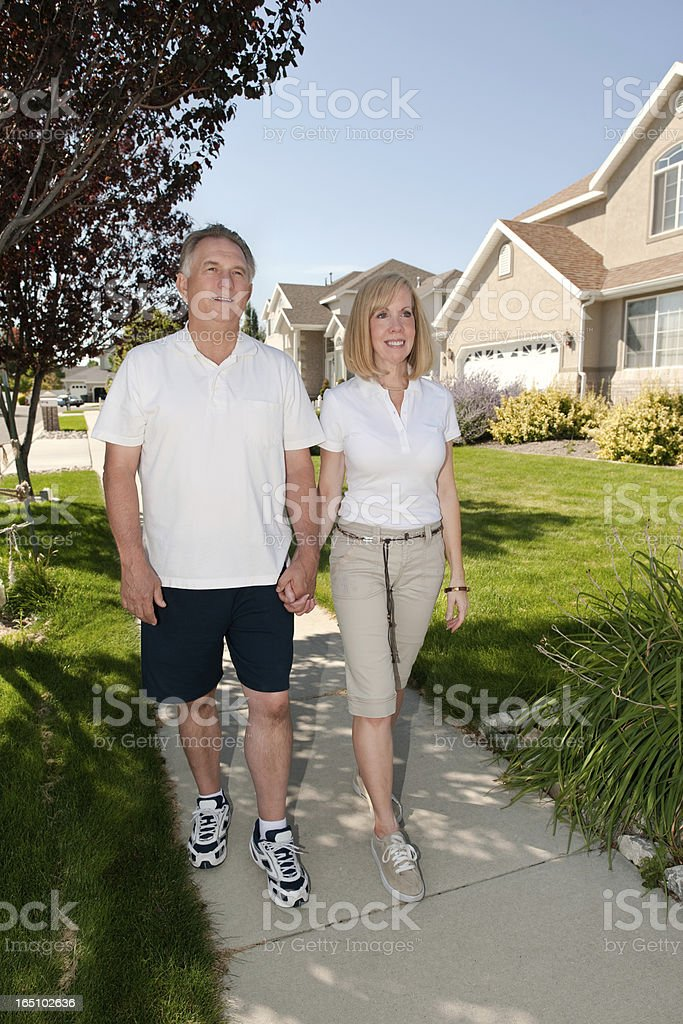 Mature Couple Walking On Sidewalk stock photo