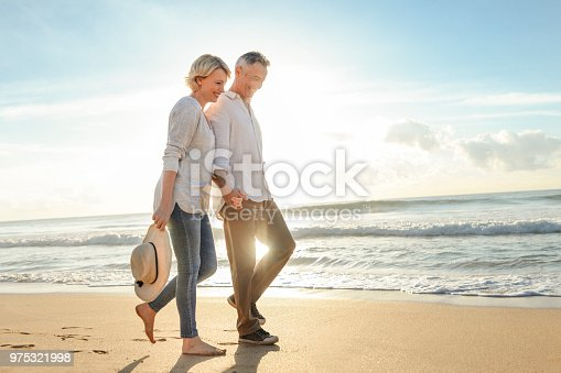 istock Mature couple walking on the beach at sunset or sunrise. 975321998