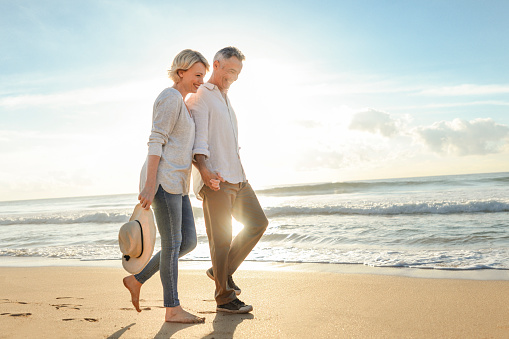 Mature couple walking on the beach at sunset or sunrise.