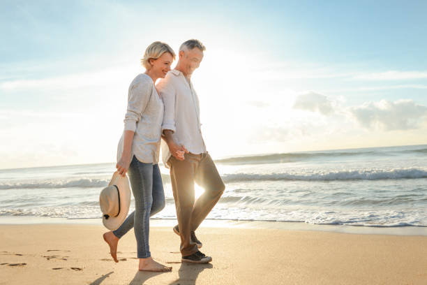 Mature couple walking on the beach at sunset or sunrise. Mature couple walking on the beach at sunset or sunrise. They are having fun, laughing and smiling. The man has grey hair. Ocean in the background. Back lit with lens flare. mature couple stock pictures, royalty-free photos & images