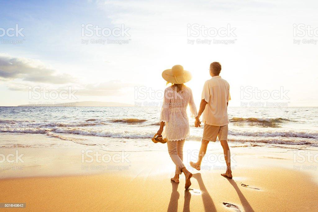 Mature Couple marchant sur la plage au coucher du soleil - Photo