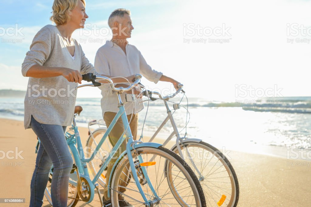 Mature couple walking their bicycles along the beach. stock photo