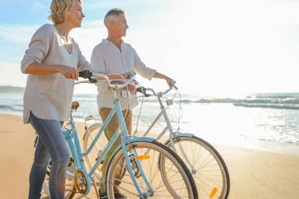 mature couple walking their bicycles along the beach. - baby boomers stock pictures, royalty-free photos & images