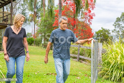 Mature couple walking together through the gate to their farmhouse
