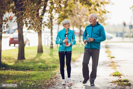 istock Mature couple walking together with water bottles 887330728