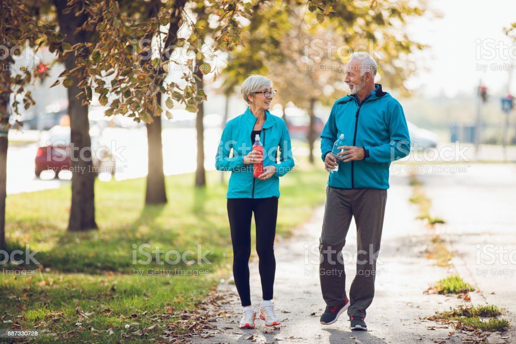 Mature couple walking together with water bottles stock photo