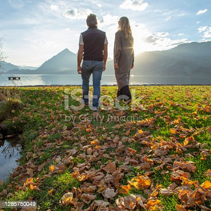 istock Mature couple walks through autumnal leaves along lakeshore at sunrise 1285750049
