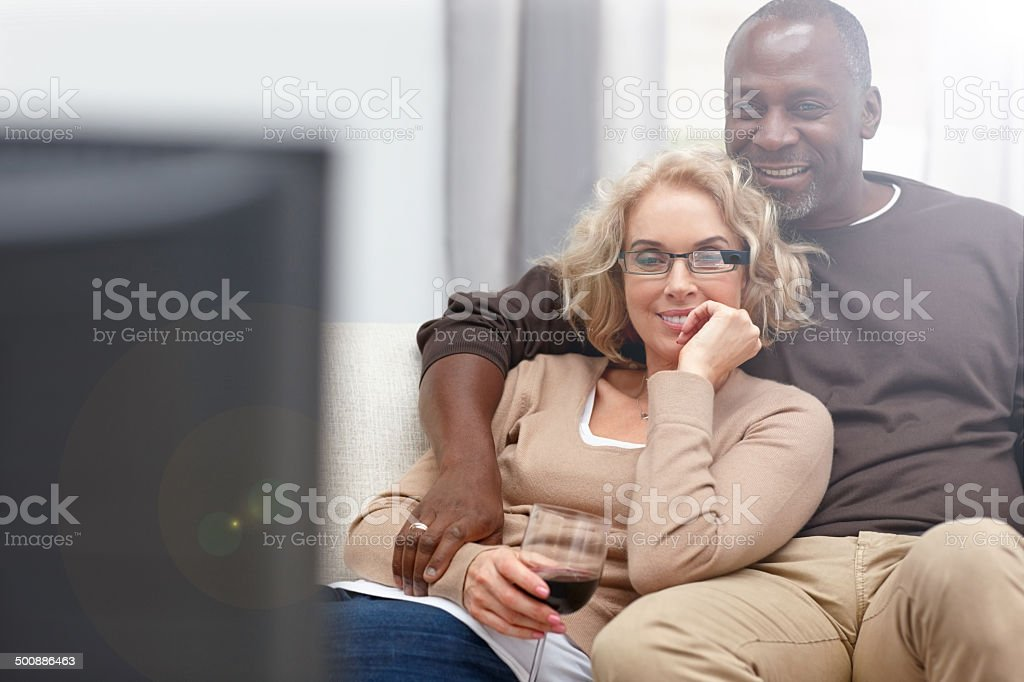 Mature couple watching romantic movie on TV stock photo
