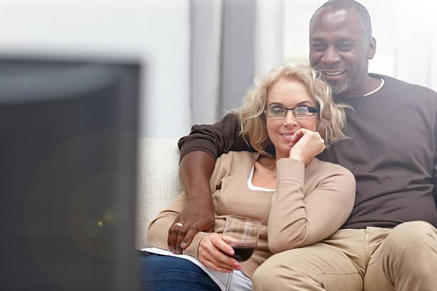Mature couple watching romantic movie on TV stock photo