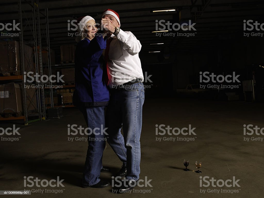 Mature couple wearing santa hats dancing in warehouse royalty-free stock photo