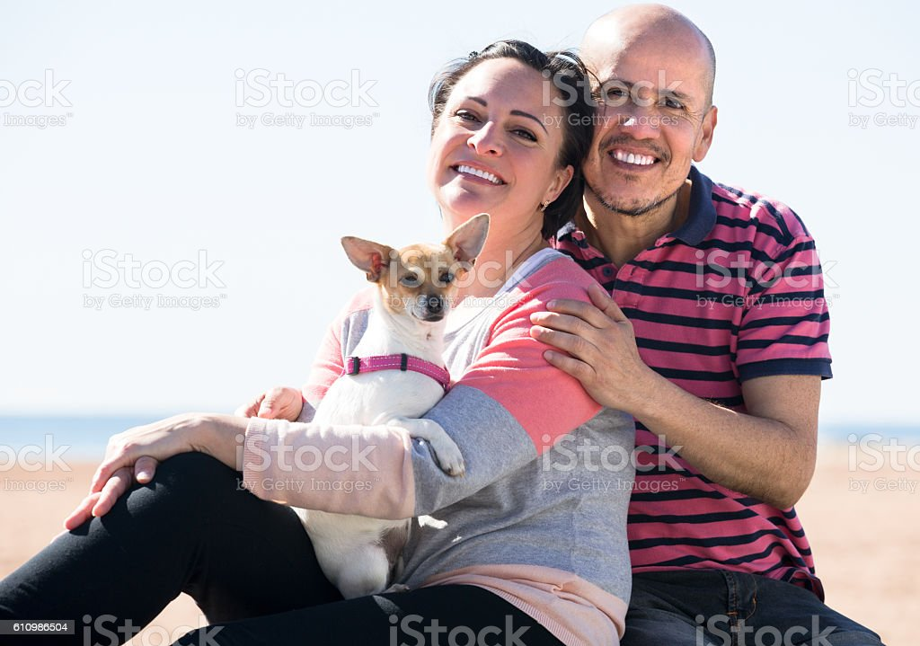 Mature couple with a small dog outdoors stock photo