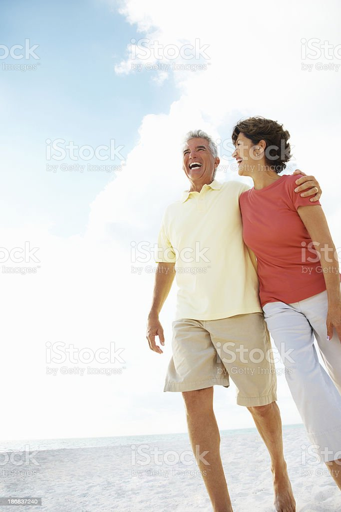 Mature couple with arms around walking on beach against sky royalty-free stock photo
