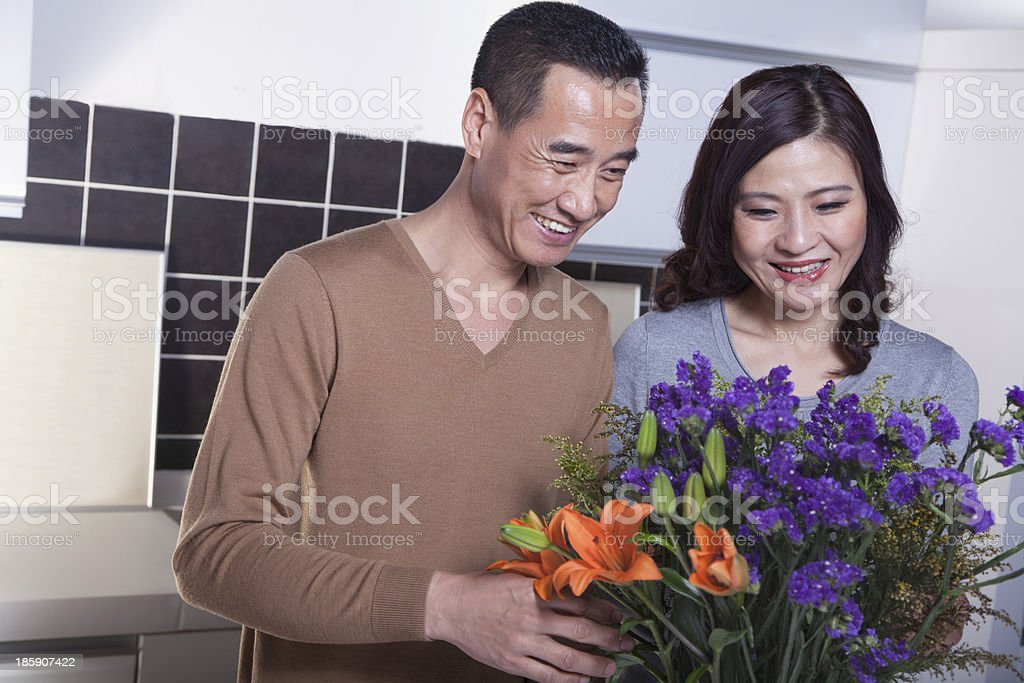Mature Couple with Bouquet of Flowers in the Kitchen royalty-free stock photo