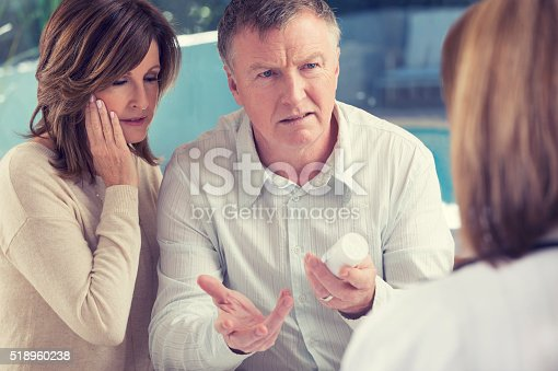istock Mature couple with doctor and medicine 518960238