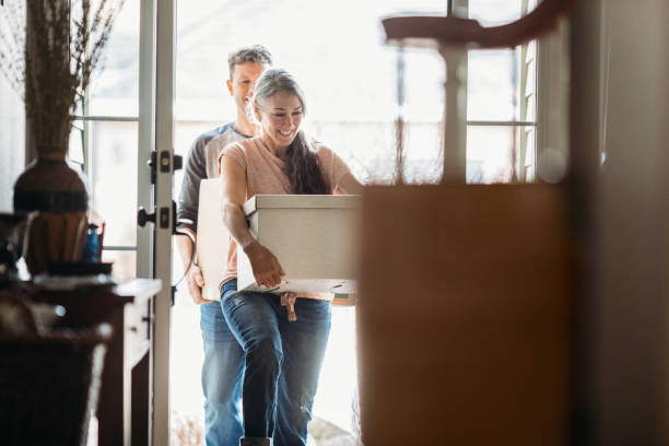 älteres paar mit umzugskartons im neuen zuhause - eigenheim stock-fotos und bilder