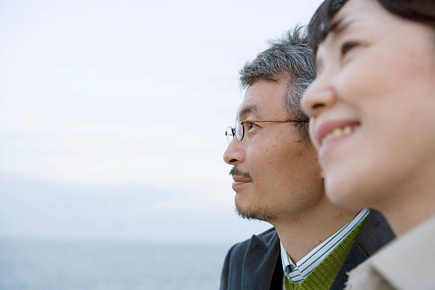 Mature couple, with sea in background, close-up, side view stock photo