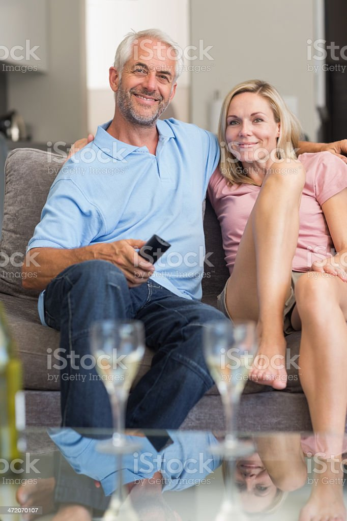 Mature couple with wine smiling and watching television royalty-free stock photo