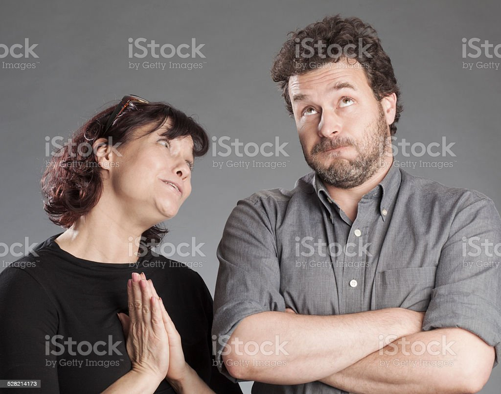 Mature couple woman asking for forgiveness man hesitating stock photo