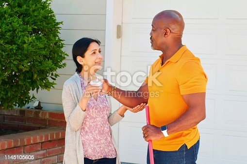 A happy mature aged mixed-race working in the front yard of their suburban home in Los Angeles, California USA.