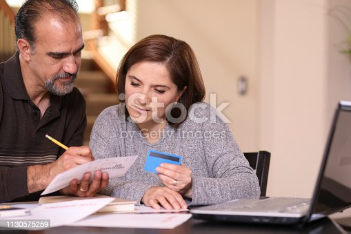 istock Mature couple working out family finances together at home. 1130575259