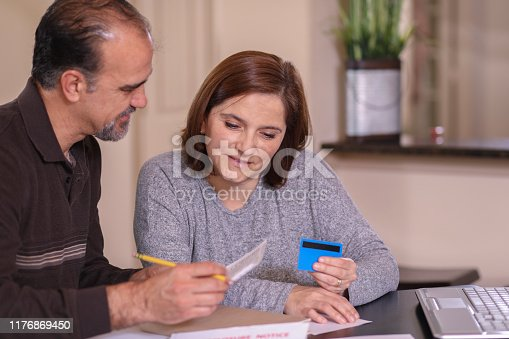 istock Mature couple working out family finances together at home. 1176869450