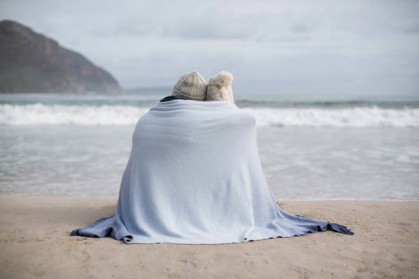 Mature couple wrapped in blanket on the beach Rear view of mature couple wrapped in blanket on the beach wrapped in a blanket stock pictures, royalty-free photos & images