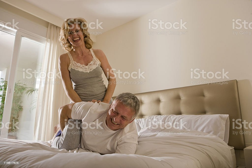Mature couple wrestling on bed stock photo