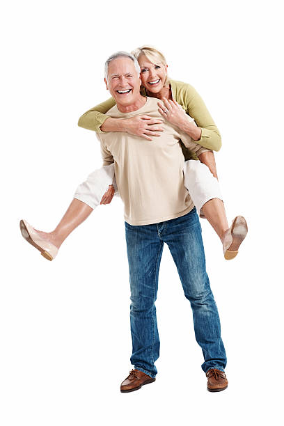 Mature couple young at heart Full length of happy mature man piggybacking woman on white background piggyback stock pictures, royalty-free photos & images