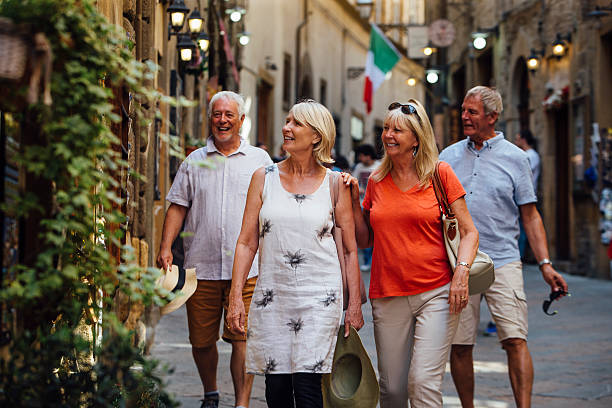mature couples looking around old town italy - europareisen stock-fotos und bilder