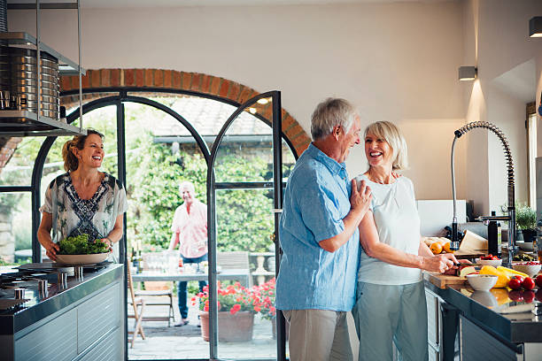 mature couples preparing for a dinner party - villa stock photos and pictures