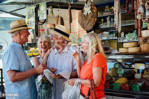 Two mature couples shopping in an Italian delicatessen. They can be seen holding some and tasting some meat. They are all smiling as they stand close together with shopping bags.