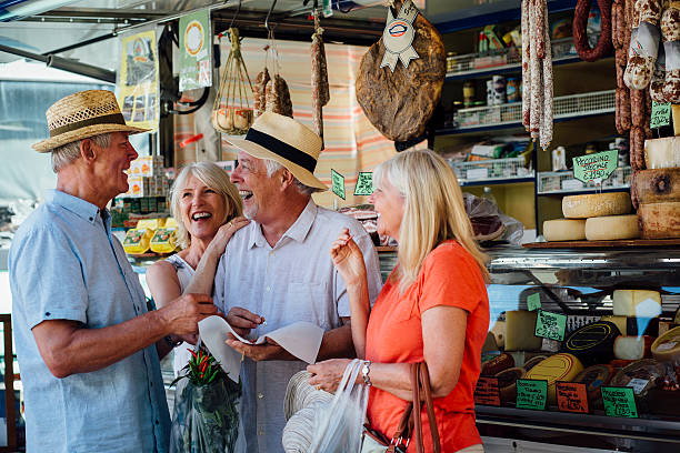 mature couples shopping in an italian delicatessen - toskana ferien stock-fotos und bilder