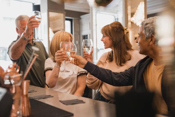 oudere paren roosteren in de bar - 50 59 jaar stockfoto's en -beelden