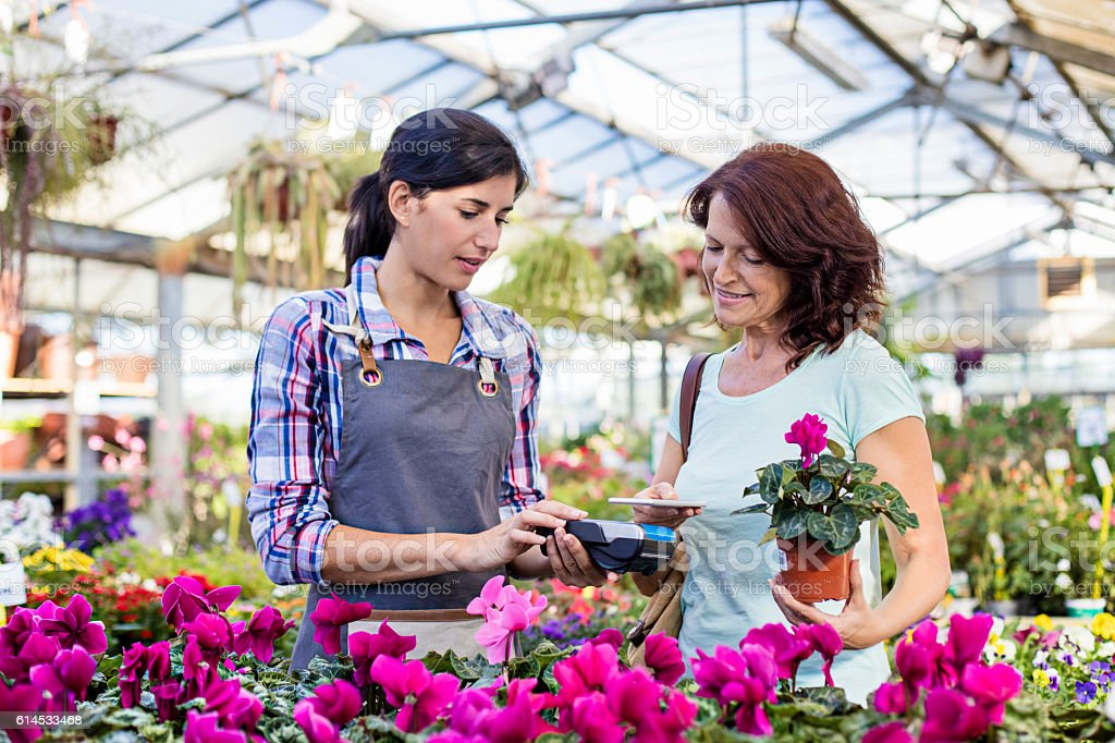 Mature customer making a contactless payment in garden center stock photo