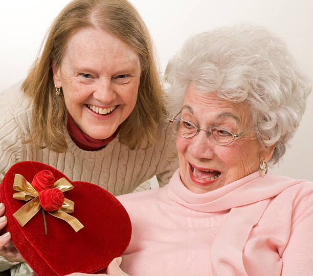 mature daughter gives her mother a valentine gift - senior valentine stock photos and pictures