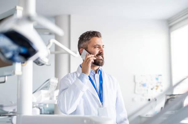 Reife Zahnarzt in der modernen Zahnchirurgie, mit Smartphone. – Foto