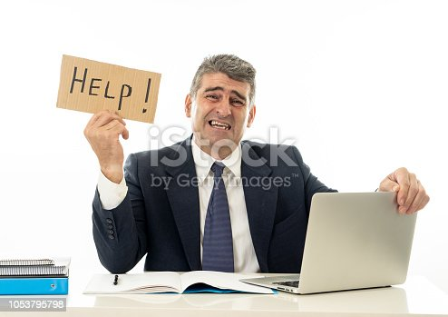 istock Mature desperate businessman suffering stress working at computer desk holding sign asking for help looking stressed overworked and helpless isolated in white background 1053795798