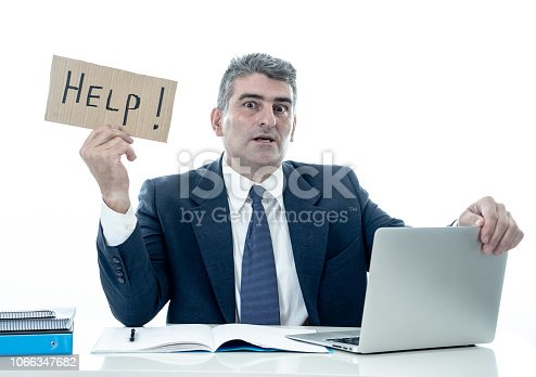 istock Mature desperate businessman suffering stress working at computer desk holding sign asking for help looking stressed overworked and helpless isolated in white background 1066347682