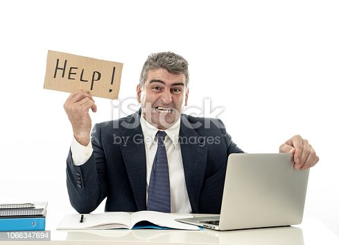 istock Mature desperate businessman suffering stress working at computer desk holding sign asking for help looking stressed overworked and helpless isolated in white background 1066347694