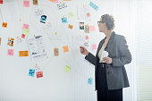 Aged woman in formalwear standing by whiteboard and learning evidence of crime