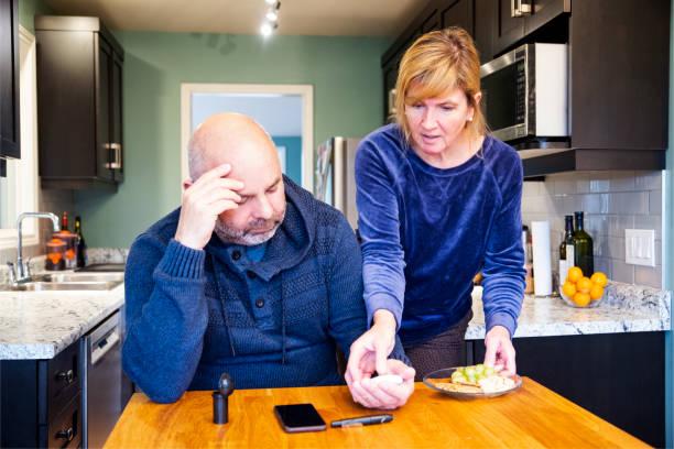 ältere diabetiker zu hause testen sein blutzuckerspiegel.  seine frau ist ihm zu hypoglykämie mit einem gesunden snack diabetiker vermeiden helfen. - hypoglykämie stock-fotos und bilder