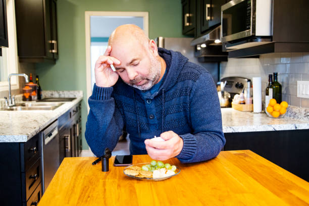 Mature diabetic patient at home testing his blood sugar, suffering from hypoglycemia Mature diabetic patient at home testing his blood sugar, suffering from hypoglycemia. hypoglycemia stock pictures, royalty-free photos & images