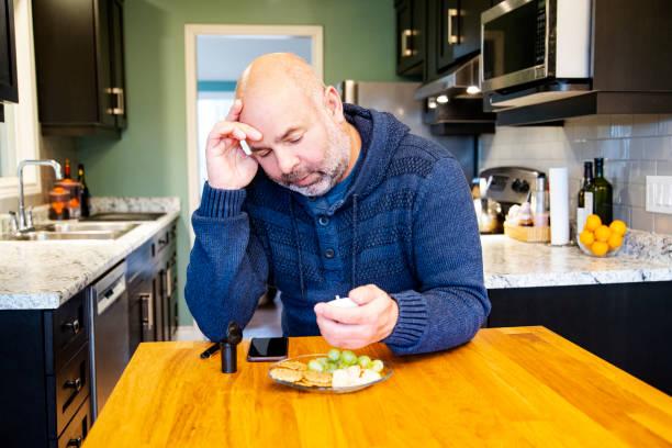 ältere diabetiker zu hause testen sein blutzuckerspiegel unter hypoglykämie leiden - hypoglykämie stock-fotos und bilder