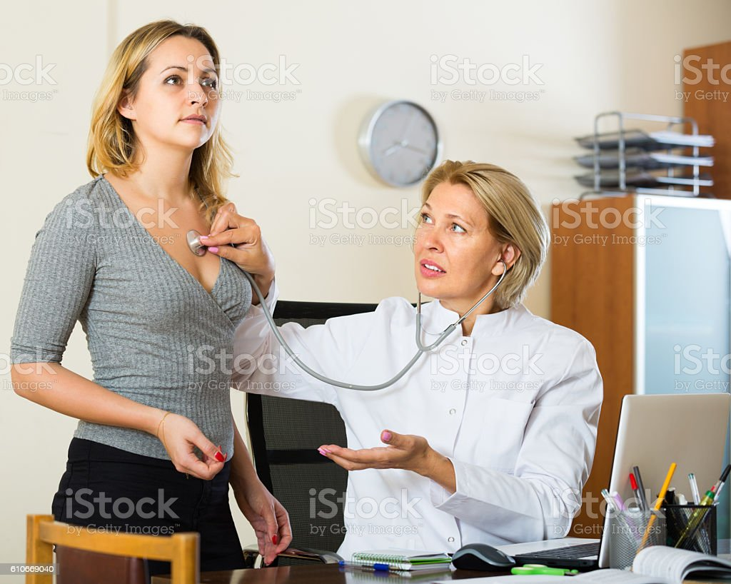 Mature doctor and ill patient stock photo