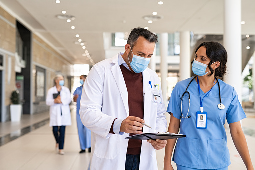 General practitioner and young nurse wearing surgical face mask against covid-19 while having a discussion in hospital hallway. Doctor with face mask discussing patient case status with his medical staff while walking on corridor. Worried busy doctor showing medical report to nurse and wearing protective face mask with copy space.